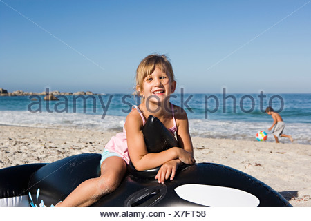 Girl 5 7 sitting on inflatable toy whale on sandy beach smiling portrait - Stock Photo