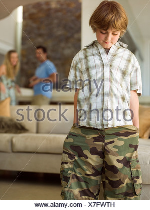 A boy standing parents in the background - Stock Photo