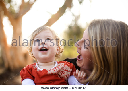 Mother holding baby daughter outdoors - Stock Photo