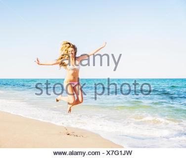 USA, Florida, Jupiter, Portrait of young woman wearing bikini jumping on beach - Stock Photo