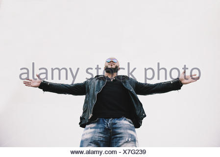 Low angle view of a cool man with arms outstretched - Stock Photo