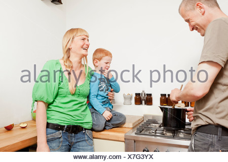 Parents cooking for reluctant son - Stock Photo