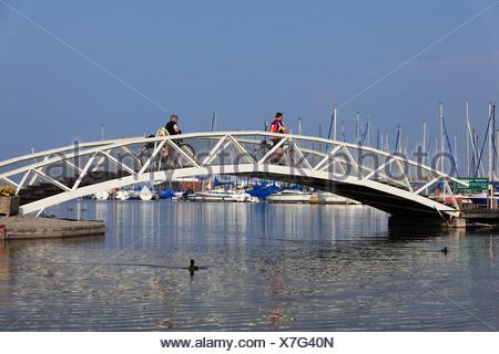 Cyclists on a bridge, Rust marina, Lake Neusiedl, Burgenland, Austria, Europe - Stock Photo