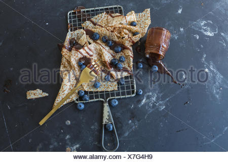 High Angle View Of Pancakes And Blueberries With Chocolate Sauce Spilled On Floor - Stock Photo