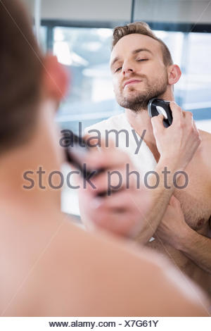Handsome man shaving in mirror - Stock Photo