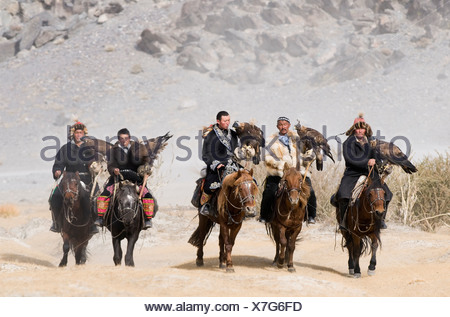 Kazakh eagle hunters with Golden Eagles on way to the Eagle Hunters Festival in Bayan-Ulgii in Altai Mountains western Mongolia - Stock Photo
