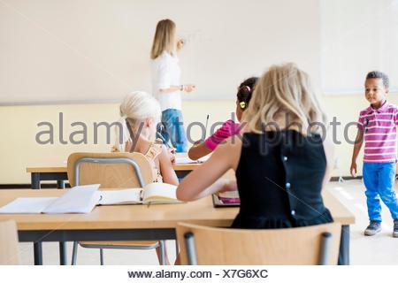 Teacher and children in classroom - Stock Photo