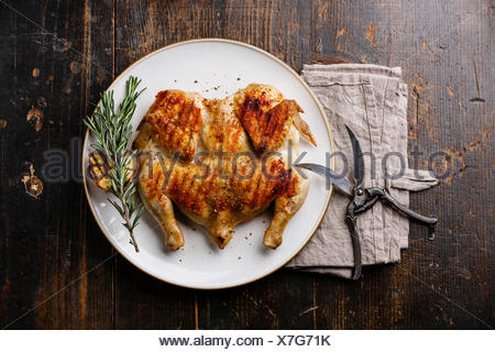 Grilled fried roast Chicken Tabaka on plate on wooden background - Stock Photo