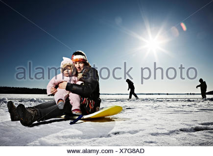 Mother and baby daughter sitting on the ice, Sweden. - Stock Photo