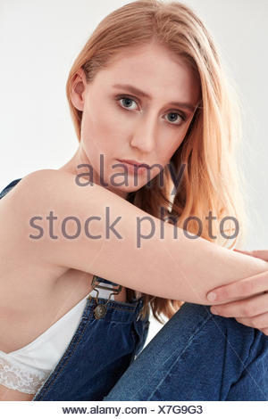 Portrait of young woman at home staring at camera - Stock Photo