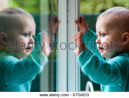 Baby boy playing with his reflection in window - Stock Photo