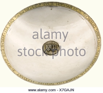 Hermann Göring and Emmy Sonnemann, a silver presentation bowl A shallow silver bowl with gilded rim, bearing a quotation from Angelus Silesius 'Die Sonne bewegt das All - Macht alle Sterne tanzen - Wirst du nicht auch bewegt - Gehörst du nicht zum Ganzen' (the sun moves everything - makes all the stars dance - if you're not moved - you don't belong to anything). In the centre there is a gilded sun with the coats of arms of Hermann Göring and his wife Emmy Sonnemann. The silversmith's mark of Professor Herbert Zeitner is in the 12 o'clock position. Marked, 'Zeit, Additional-Rights-Clearances-NA - Stock Photo
