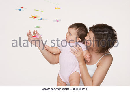 Woman and baby looking at mobile - Stock Photo
