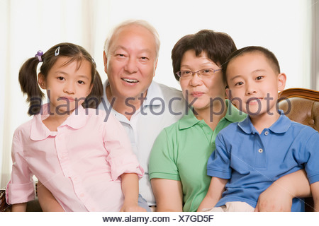 Portrait of a mature couple smiling with their grandchildren - Stock Photo