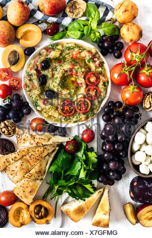 Eggplant babaganoush with red bell pepper and herbs on a snack board full of summer fruit photographed from top view. - Stock Photo