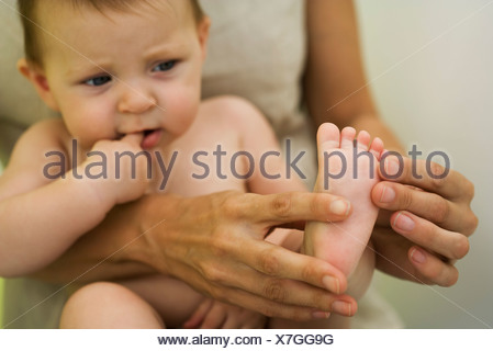 Mother holding baby on lap, playing with baby's foot, cropped - Stock Photo