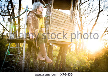 Mature woman looking out from woodland treehouse at sunset - Stock Photo