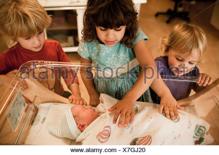 Siblings looking at newborn baby brother in hospital - Stock Photo