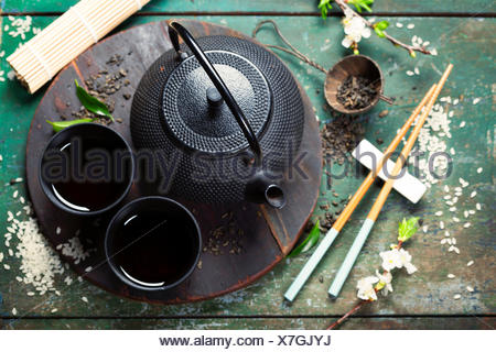 Chinese Tea Set and chopsticks on rustic wooden table - Stock Photo