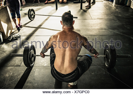 Mid adult man preparing to lift barbell in gymnasium - Stock Photo