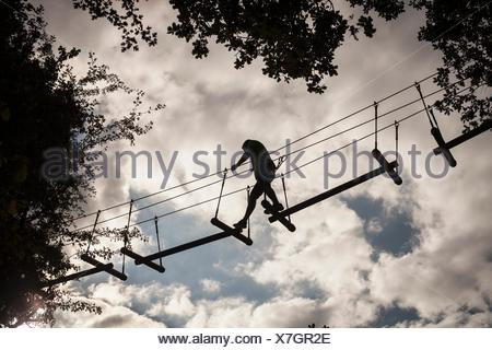 Mature man, high rope walking, low angle view - Stock Photo