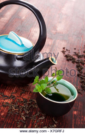 Traditional tea background. Tea in tea bowl with fresh mint herb, ceramic tea pot, dry tea crop on brown wooden background. Asian tea drinking ceremony. - Stock Photo