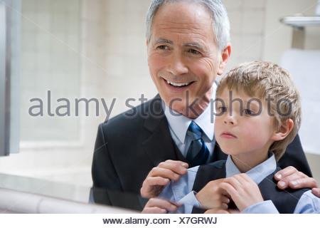 Man helping grandson to tie his tie - Stock Photo