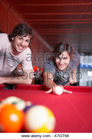 Two men playing pool and smiling - Stock Photo