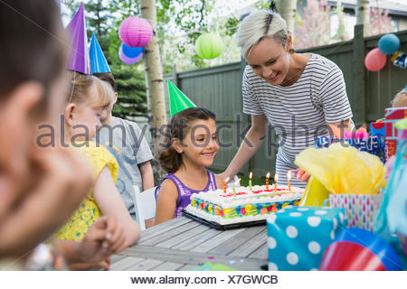 Mother lighting birthday candles cake for daughter party - Stock Photo