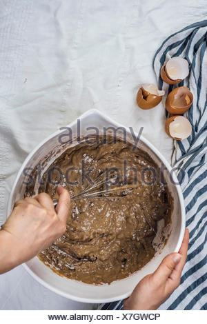 A woman mixing a cake batter in a large bowl photographed from top view. Egg shells are on the side. - Stock Photo