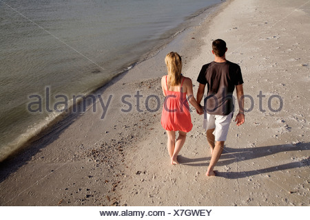 Young couple walking along beach, elevated view - Stock Photo