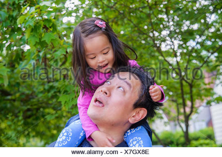 Mid adult father shoulder carrying toddler daughter - Stock Photo