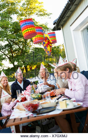 Sweden, Sodermanland, Jarna, Family with small child (2-3) sitting at table celebrating Crayfish Party - Stock Photo