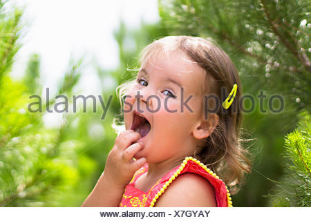 Girl with hand on face laughing - Stock Photo
