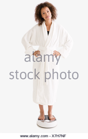 Woman standing on bathroom scales - Stock Photo