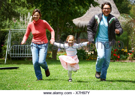 happy family smiling and running outdoors towards the camera - Stock Photo