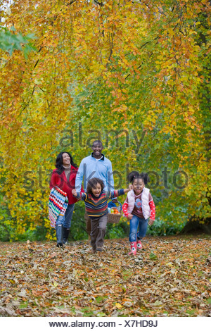 Happy family walking in park of autumn leaves with picnic basket - Stock Photo