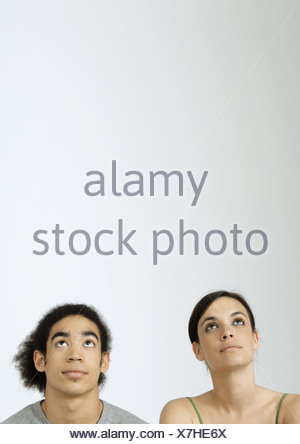 Young couple looking up, portrait - Stock Photo
