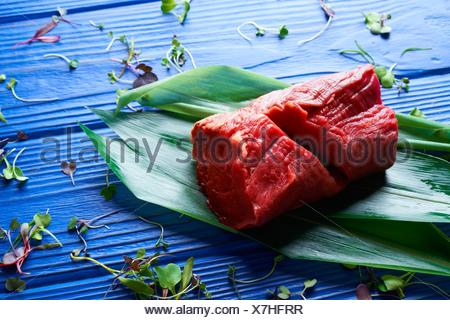 Beef meat loaf Veal loin on blue wood background. - Stock Photo