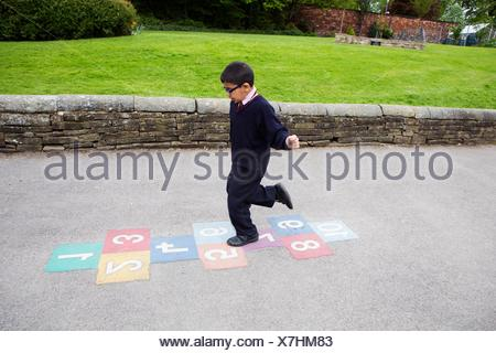 Boy playing hopscotch in playground - Stock Photo