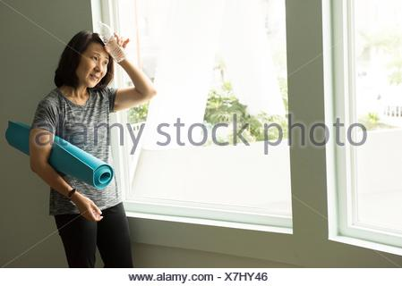 Mature woman holding bottle of water to forehead looking away - Stock Photo