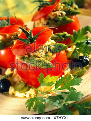 Tomatoes stuffed with hard-boiled egg yolk, caper and mixed herb mayonnaise - Stock Photo