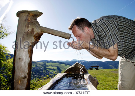 A man in his mid 40 quenches his thirst at a well, Todtnauberg in the Black Forest, Baden-Wuerttemberg, Germany, Europe - Stock Photo