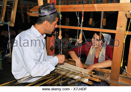 Silk production, Usbek man and woman working on a wooden loom, Silk Road, Fergana Valley, Uzbekistan, Central Asia - Stock Photo