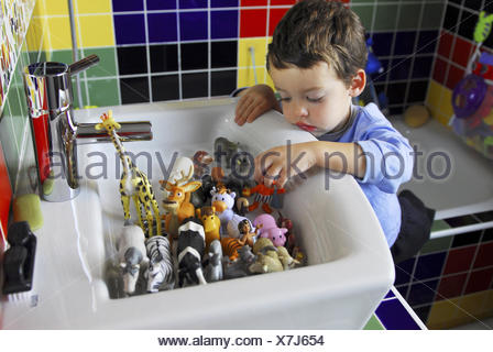 Baby boy four years old playing with animal toys in a bathroom, Madrid. - Stock Photo