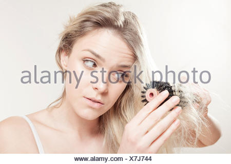 Young woman brushing her hair - Stock Photo
