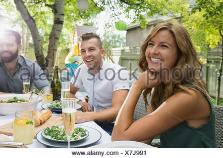 Smiling friends enjoying garden party lunch - Stock Photo