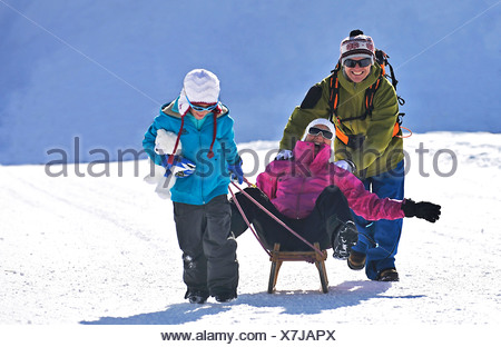 mother sitting on a sled having fun being pulled by her husband and her son, France - Stock Photo