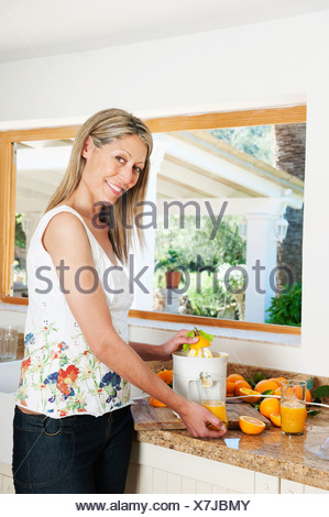 Woman using a juicer in kitchen - Stock Photo