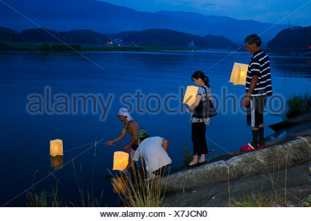 People place candle-lit lanterns in the water during Obon. - Stock Photo